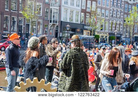 AMSTERDAM-APRIL 27: Unidentified people on the boat at the open-air party during King's Day Singel canal on April 272015 the Netherlands. King's Day is the largest open-air festivity in Amsterdam.