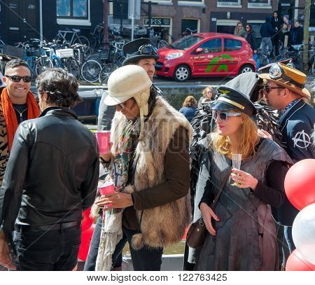 AMSTERDAM-APRIL 27: Unidentified locals celebrate King's Day the Singel canal on April 272015 the Netherlands. King's Day is the largest open-air festivity in Amsterdam.