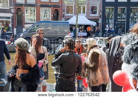AMSTERDAM-APRIL 27: Unidentified people in the sunny day at the open-air party celebrate King's Day on the Singel canal on April 272015. King's Day is the largest open-air festivity in Amsterdam.
