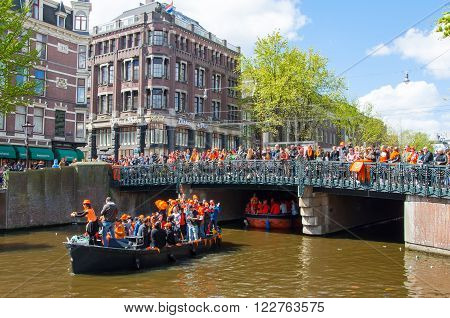 AMSTERDAM-APRIL 27: King's Day also known Koningsdag on the Singel canal people watch the festival on the bridge on April 27 2015. King's Day is held on 27 April every year.