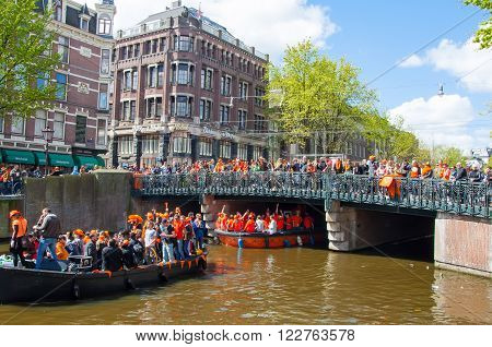 AMSTERDAM-APRIL 27: King's Day (Koningsdag) boating on the Singel canal crowd of people watch the festival on the bridge on April 27 2015. King's Day is held on 27 April every year.