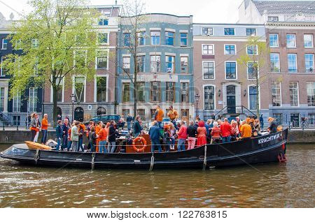 AMSTERDAM-APRIL 27: Locals and tourists have dance party on a boat King's Day along the Singel canal on April 272015 the Netherlands. King's Day is the largest open-air festivity in Amsterdam.