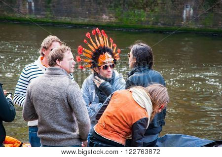 AMSTERDAM-APRIL 27: Undefined people in traditional orange celebrate King's Day on the Singel canal on April 272015 in Amsterdam the Netherlands