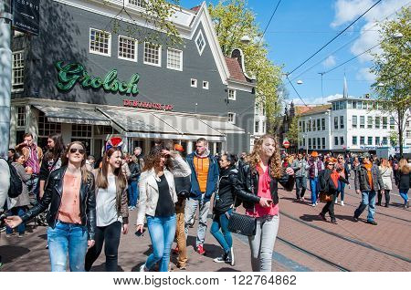 AMSTERDAM-APRIL 27: Young people celebrate the King's Day on Amsterdam street on April 272015 the Netherlands. King's Day (Koningsdag) is held on 27 April (the king's birthday) every year.