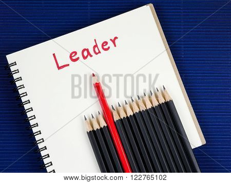 Red pencil standout from black pencil and handwriting word Leader on blank notebook with blue corrugate paper background leadership business concept