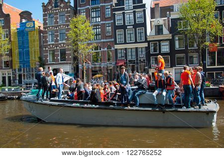 AMSTERDAM, NETHERLANDS - APRIL 27: Boat party along Amsterdam's canals during King's Day on April 27, 2015 in Amsterdam.King's Day is the largest open-air festivity in Amsterdam the Netherlands.