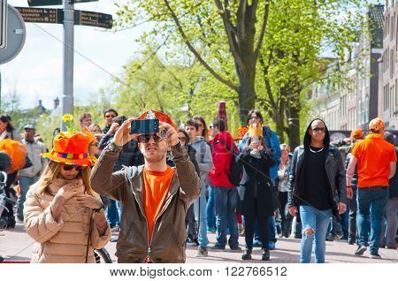 AMSTERDAMNETHERLANDS-APRIL 27: Locals and tourists in orange on the street on King's Day on April 2727 in Amsterdam. King's Day is the largest open-air festivity in Amsterdam.