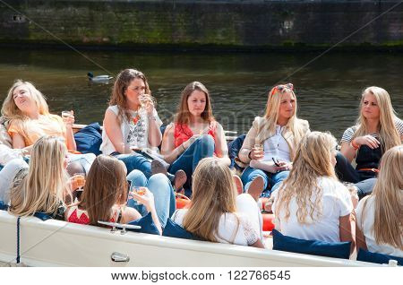 AMSTERDAMNETHERLANDS-APRIL 27: Local girls celebrate King's Day in a boat on April 272015 in Amsterdam the Netherlands. King's Day is the largest open-air festivity in Amsterdam.