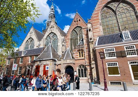 Amsterdam-April 27: Oude Kerk in Amsterdam's red-light district tourists go sightseeing on April 272015 the Netherlands. The Oude Kerk is Amsterdam's oldest parish church consecrated in 1306.