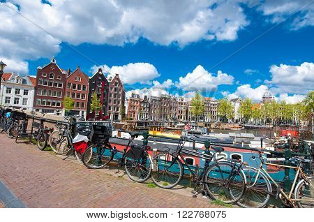 Amsterdam the Netherlands-April 27: Traditional Amsterdam cityscape with medival houses bikes on the bridge on April 272015. Amsterdam is the most populous city of the Kingdom of the Netherlands.