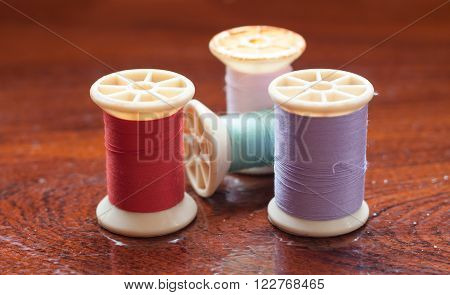 Vintage grunge colorful thread spool on wooden table, stock photo