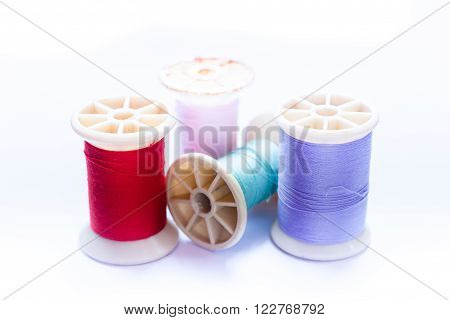 Vintage grunge colorful thread spool on white background, stock photo