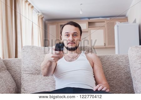 man sprawled on the couch with the remote