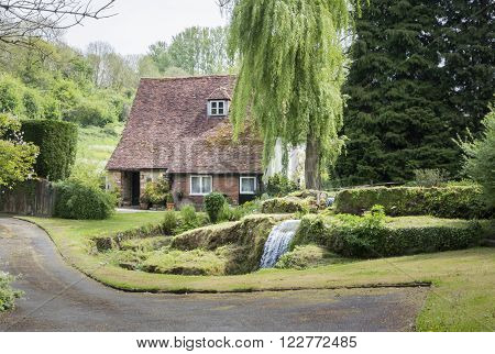 LOOSE KENT UK 11 MAY 2015 - Old cottage with waterfall in the garden in the pretty village of Loose Kent UK