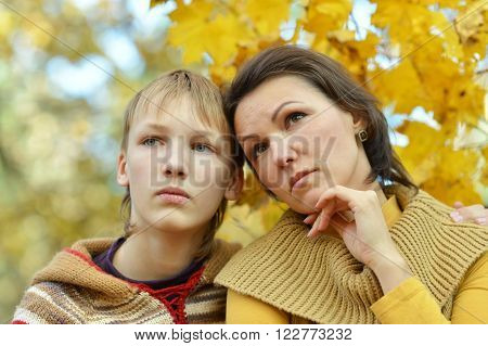 Sad mother with a son in the autumn park
