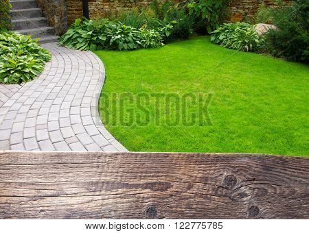 Garden stone path with grass growing up between the stones. Wooden background for text.