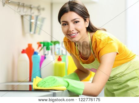 Beautiful woman in protective gloves cleaning electric range with rag