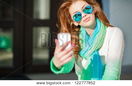 Young beautiful woman with red curly long hair,light makeup and pink nail Polish,dressed in a knitted sweater white-green color,the neck is blue-green scarf,is making selfie on mobile phone in fall city,wears mirrored blue glasses
