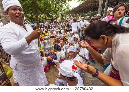 SANUR, BALI - MAR 18, 2016: Unidentified people during Melasti Ritual - one of the most important rituals of Bali was meant as the ritual to cleanse the world from all the filth of sin and bad karma.