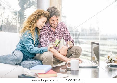Cheerful couple looking at computer while relaxing on the couch woman holding a credit card - Online shopping people purchasing new gift from e-commerce website