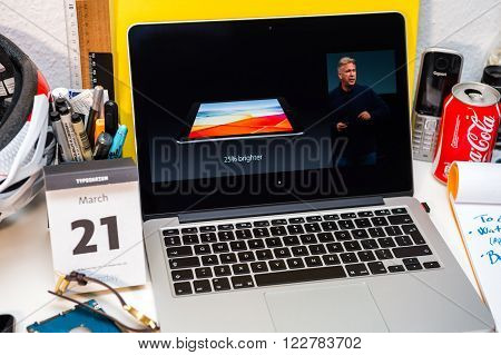 PARIS FRANCE - MARCH 21 2016: Apple Computers website on MacBook Pro Retina in a creative room environment showcasing Apple Event with 25% brighter display