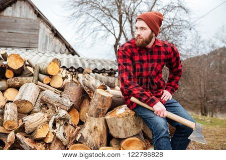 Lumberjack with axe resting outdoors and looking away
