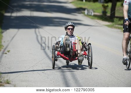 DIGHTON MASSACHUSETTS AUGUST 7 2010: Rider on a recumbent tricycle enjoys a short downhill in Pan-Mass Challenge charity ride for cancer research and patient care at Dana-Farber Cancer Institute