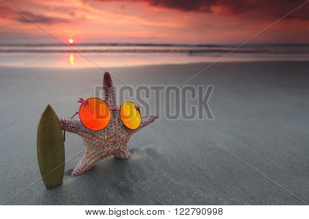Starfish surfer on the beach and beautiful sunset over sea