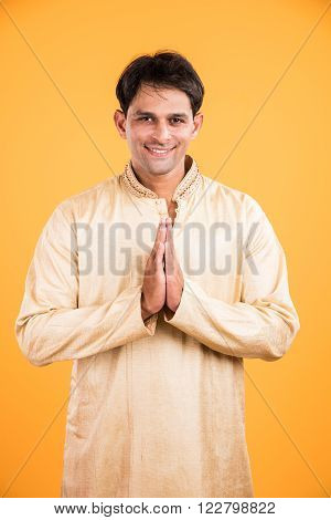 portrait of an Indian man standing in a prayer position, isolated over yellow background. Indian man in welcoming gesture, indian man in namaskar pose, indian male model and ethnic wear