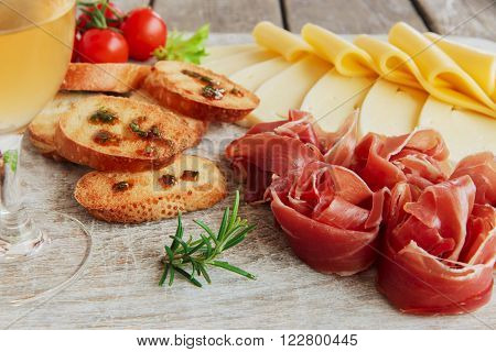delicious appetizer to wine - ham,prosciutto, cheese, capers, tomato, served on a light wooden board