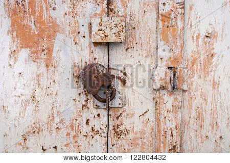 Steel lock on the rusty grey metal door. close-up. focus on lock