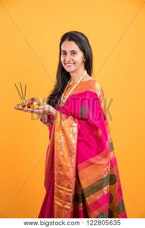 Indian woman performing puja, indian girl with pooja thali or puja thali, portrait of a beautiful young lady with pooja thali, isolated over yellow background