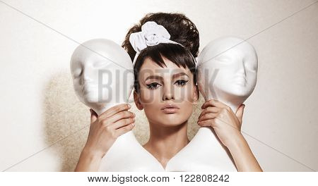 Beautiful brunette woman with retro hairdo. Luxury vogue style model holding white mannequins. Love triangle concept.
