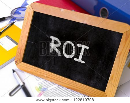 Handwritten ROI -  Return on Investment - on a Chalkboard. Composition with Chalkboard and Ring Binders, Office Supplies, Reports on Blurred Background. Toned Image. 3D Render.