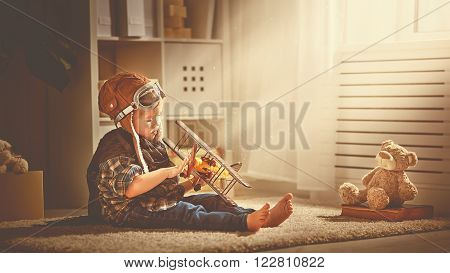 concept of children's dreams and travels. pilot aviator child with a toy airplane plays at home in his room ** Note: Soft Focus at 100%, best at smaller sizes