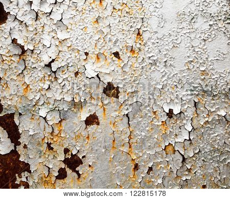 Rusty metal surface with cracked gray paint.