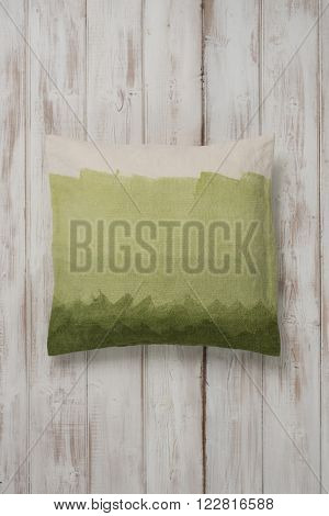 Square Gradient Green Throw Pillow Laid Flat On Wooden Surface