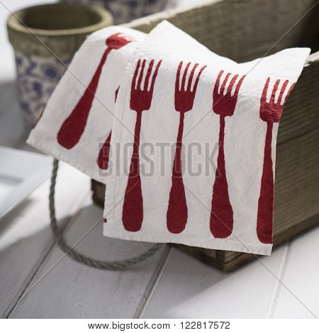 White Dinner Napkin With Red Fork Design On Small Crate