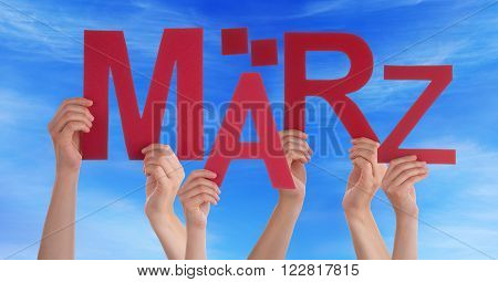 Many Caucasian People And Hands Holding Red Letters Or Characters Building The German Word Maerz Which Means March On Blue Sky