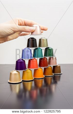 Colorful coffee capsules placed in form of pyramid.