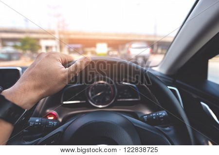 Man's hands of a driver on a modern car on the road. Vintage style processed