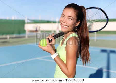 Happy tennis player girl holding tennis racket / racquet and ball on outdoor court portrait. Asian young woman fitness trainer ready for playing game match during summer. Sports activity.