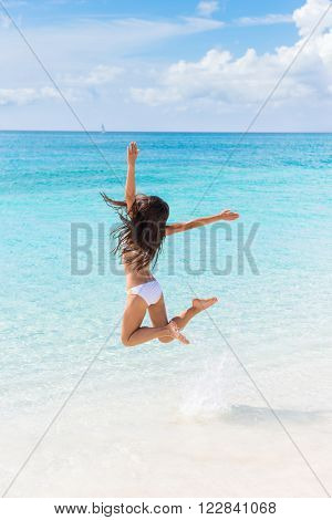 Beach vacation success woman jumping of joy and happiness cheering winning splashing water in ocean. Winner girl from behind with arms up in the air cheerful enjoying summer vacations travel.