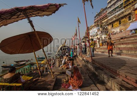 VARANASI, INDIA - APRIL 18, 2010: Crowd of local Indian live their morning life with Ganga river in Varanasi, India. The most holy river of India and Hindu culture.