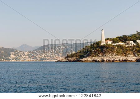 Color DSLR stock image of a lighthouse and houses along the Mediterranean coast of the French Riviera near Nice, France. Horizontal with copy space for text