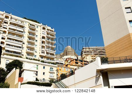 Color DSLR stock image of luxury apartment buildings in Monte Carlo in Monaco on the French Riviera, with a clear blue sky background. Horizontal with copy space for text