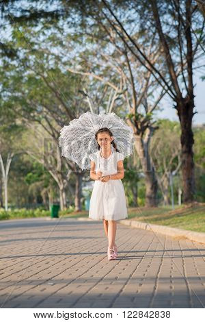Girl with white lace umbrella walking in summer park