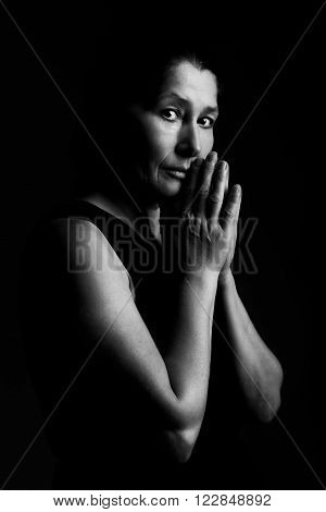Beautiful woman prays doing different expressions on a black background