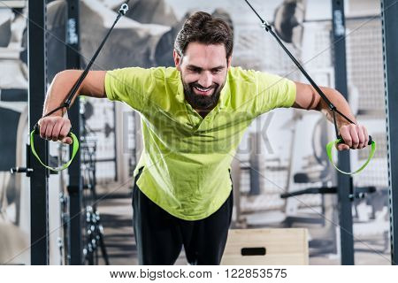 Man doing pushup with rings in functional training gym