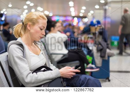 Casual blond young woman using her cell phone while waiting to board a plane at the departure gates. Wireless network hotspot enabling people to access internet conection. Public transport.